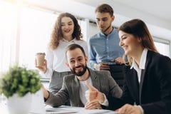 Det härliga affärsfolket använder datorer och ler, medan arbeta i regeringsställning royaltyfri fotografi
