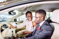 Det härliga afrikanska paret väljer den nya bilen på återförsäljaren Arkivbild