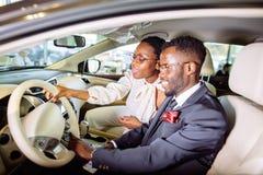 Det härliga afrikanska paret väljer den nya bilen på återförsäljaren Royaltyfria Bilder