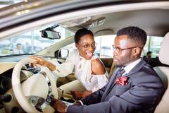 Det härliga afrikanska paret väljer den nya bilen på återförsäljaren Royaltyfri Foto
