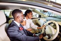 Det härliga afrikanska paret väljer den nya bilen på återförsäljaren Royaltyfri Fotografi