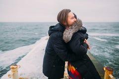 Det härliga barnet kopplar ihop ömt att krama på den asfulla pir under regnig höstdag Vinterhavsbakgrund Arkivbilder
