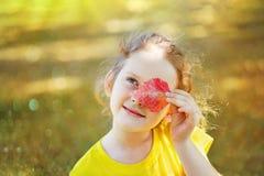 Det härliga barnet med sidor synar i guld- höst parkerar Arkivbild