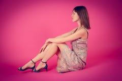 Det härliga barnet modellerar en rosa fransk klänningrosa färgbakgrund Arkivfoton