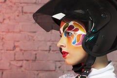 Det härliga barnet modellerar med ljust idérikt smink med hjälmen Arkivbilder
