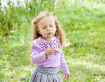 Det härliga barnet slår på maskrosen i sommaren Royaltyfri Foto