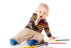 Det härliga barnet tecknar med blyertspennor arkivfoto