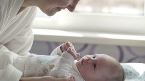Det härliga barnmoderleendet och kysser hennes barn stock video