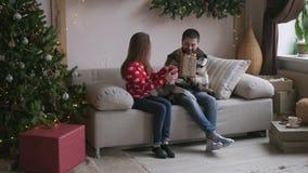 Det härliga barnparet firar hemma Den nätta flickan ger hennes pojkvän en gåvaask lager videofilmer