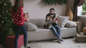 Det härliga barnparet firar hemma Den nätta flickan ger hennes pojkvän en gåvaask stock video