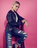 Det härliga blonda barnet modellerar att posera i svart läderomslag och b Arkivfoto