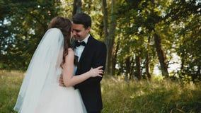 Det härliga bröllopparet i omfamning smeker sig på naturen stock video