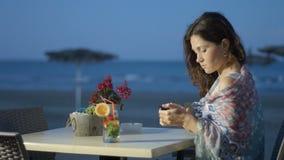 Det härliga eleganta maskinskrivningmeddelandet för den unga damen på smartphonen, kopplar av på strandkafét arkivfilmer
