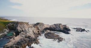 Det härliga filmiska flyg- skottet av idylliska havvågor som kraschar över stort, vaggar på sommarBig Surkusten Kalifornien lager videofilmer