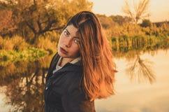 Det härliga flickaanseendet nära sjön i höst parkerar royaltyfri foto