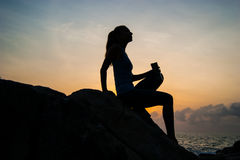 Det härliga flickasammanträdet på stenar och se i ett avstånd, flickan på solnedgången för att meditera i tystnad, härlig kropp B royaltyfria foton