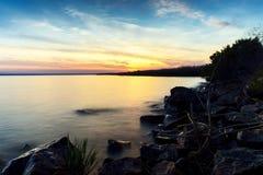 Det härliga flodlandskapet med vaggar på solnedgången, solen går bejen Arkivbilder