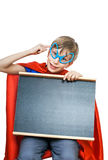 Det härliga gladlynta barnet som kläs som stålman med roliga exponeringsglas, rymmer en rektangulär svart tavla arkivfoto