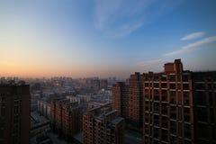 Det härliga landskapet av staden på bakgrunden av den orange solnedgången Royaltyfri Bild