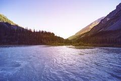 Det härliga landskapet med högt vaggar med upplysta maxima, stenar i bergsjön, reflexion, blå himmel och gult solljus in royaltyfri foto
