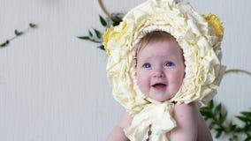 Det härliga lilla barnet som bär den gula huvudbonaden, poserar på kameran på photoshoot arkivfilmer