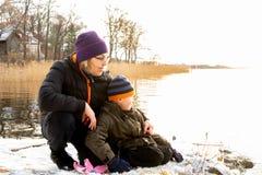 Det härliga ljusa vinterlandskapet vid havet med en kvinna och barnet som sitter i snön på, vaggar att se över vattnet royaltyfri bild