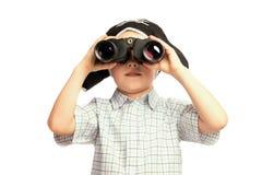 Barnet piratkopierar in hatten som ser i kikare Arkivbilder