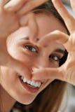 Det härliga lyckliga tecknet för kvinnavisningförälskelse nära synar Royaltyfri Foto