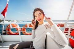 Det härliga modellflickanederlaget från det ljusa soltidningssammanträdet på en fartygkryssning snubblar turisten Royaltyfri Foto