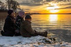 Det härliga orange vinterlandskapet vid havet med en kvinna och barn som sitter i snön på, vaggar att se en beträffande ljus soln royaltyfri fotografi