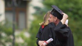 Det härliga paret i akademiker klär att krama med förälskelse och att skratta glatt arkivfilmer
