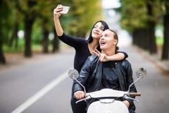 Det härliga paret i solexponeringsglas gör selfie genom att använda en smart telefon och le, medan sitta på en sparkcykel utomhus royaltyfri bild