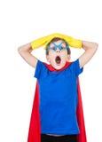 Det härliga roliga barnet klädde som superheroen som ser förvånad arkivfoto