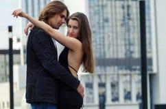 Det härliga sinnliga eleganta paret står på en stadsgata och emb Arkivfoton