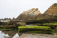 Det härliga slutet upp på vaggar på den sandiga vulkaniska azkorristranden nära bilbao på spansk atlantisk kust i det basque land Royaltyfria Foton