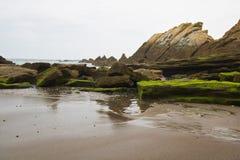 Det härliga slutet upp på vaggar på den sandiga vulkaniska azkorristranden nära bilbao på spansk atlantisk kust i det basque land Royaltyfria Bilder