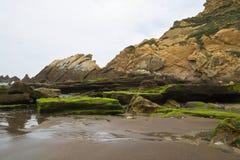 Det härliga slutet upp på vaggar på den sandiga vulkaniska azkorristranden nära bilbao på spansk atlantisk kust i det basque land Arkivbild