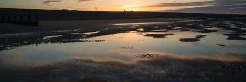 Det härliga soluppgångpanoramalandskapet reflekterade i tips på stranden Fotografering för Bildbyråer