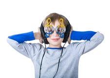 Det härliga stilfulla blonda barnet som bär stor yrkesmässig hörlurar och roliga exponeringsglas, lyssnar till musik royaltyfri bild