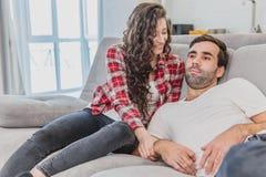 Det härliga unga gifta paret håller ögonen på tv med glädje De sitter på soffan och att omfamna Mannen rymmer arkivbild