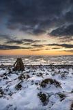 Det härliga vinterlandskapet på den vibrerande solnedgången över snö täckte c Arkivbild