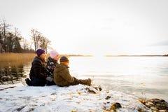 Det härliga vinterlandskapet vid havet med en kvinna och barn som sitter i snön på, vaggar att se en ljus solnedgångreflectin royaltyfria foton