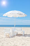 Det härliga vita den strandparaplyet och solen bäddar ned på en solig strand. Arkivbilder