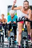 Det höga folket i idrottshallsnurr på kondition cyklar Arkivfoton