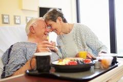 Det höga paret i sjukhusrum som den manliga patienten har lunch Fotografering för Bildbyråer
