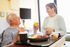 Det höga paret i sjukhusrum som den manliga patienten har lunch arkivbilder