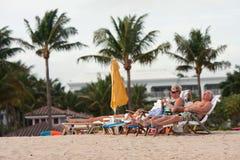Det höga paret kopplar av i strandstolar på den Florida semesterorten arkivfoton