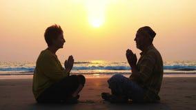 Det höga paret sitter och meditera tillsammans på den sandiga stranden arkivfilmer