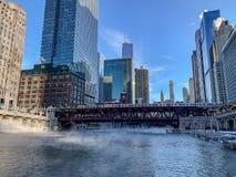 Det höjde drevet korsar ett frysa Chicago River som ångalöneförhöjningar, medan temperaturer rasar royaltyfri bild