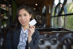 Det h?rliga asiatiska leendet och h?ll f?r aff?rskvinna f?rbig?r den vita aff?ren eller kreditkorten som isoleras p? vit bakgrund arkivbild